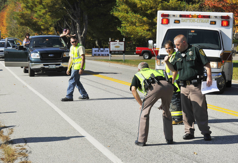 Sgt. Roger Hicks of the York County Sheriff's Office examines skid marks at the scene of a crash at Gould and New County roads in Dayton on Monday. Seven people were hospitalized with injuries that didn't appear life-threatening, Hicks said.