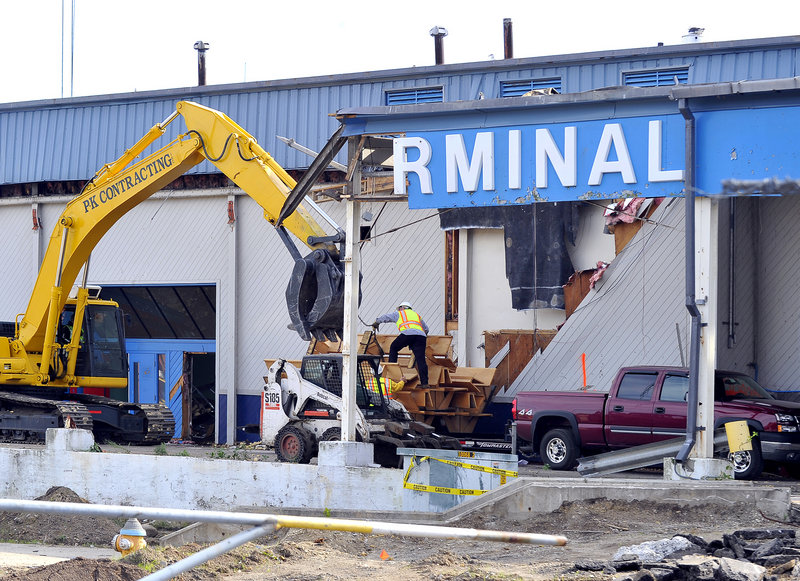 Workers are demolishing the International Marine Terminal as part of an expansion project that also involves razing a U.S. Customs building, expanding the pier and constructing a new port operations building on Commercial Street.