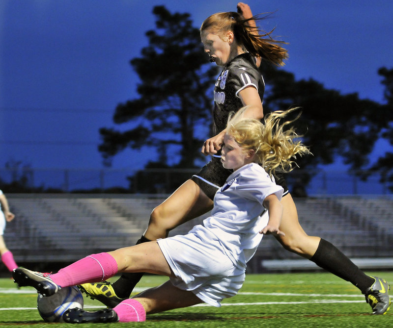 Meaghan Wells of Deering slides to try and keep the ball away from Abby Hyson of Marshwood during their Western Class A girls' soccer game Tuesday night at Deering High. Deering earned a 3-0 victory.