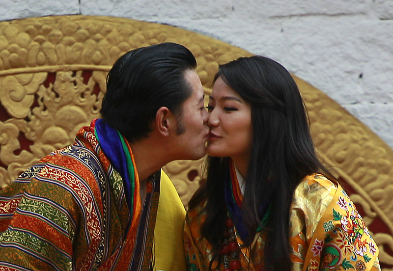 Bhutan's King Jigme Khesar Namgyal Wangchuck and Queen Jetsun Pema kiss in front of the crowd at a stadium as part of their wedding celebration in Bhutan on Saturday.