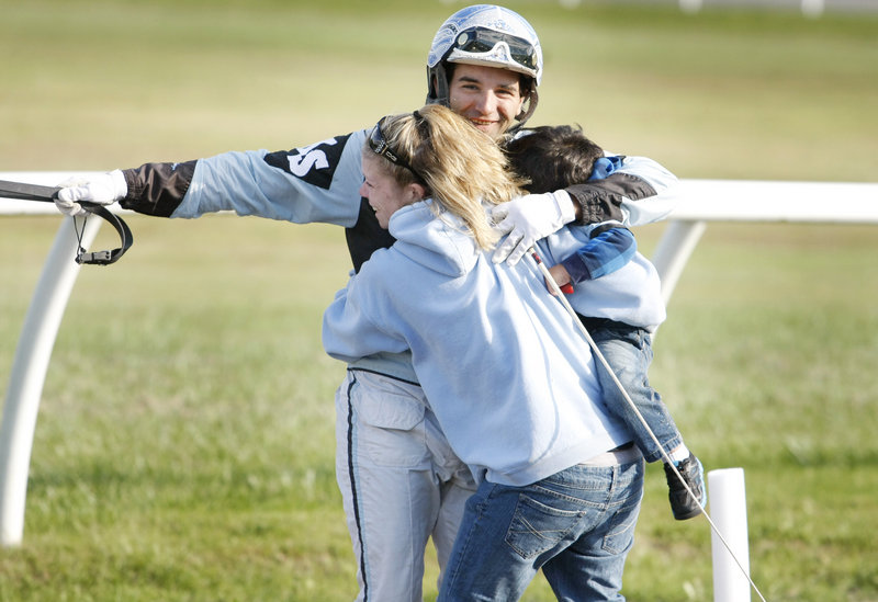 Kevin Switzer Jr. is greeted by his wife, Liz Switzer, and son Garrett, 2, as he makes his way to the winner's circle after riding CBF Fancy to the victory.