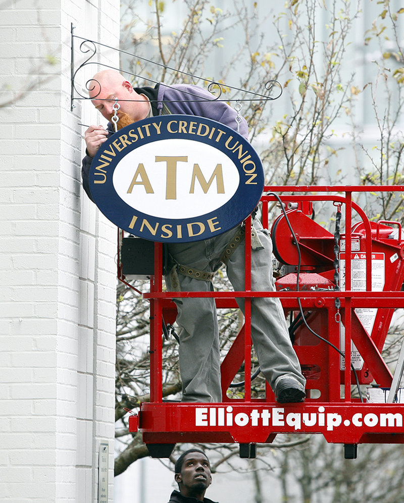 Shawn Butler of Sign Design Inc. paints the edges of a new sign after installing it outside the Robert L. Woodbury Campus Center on the University of Southern Maine campus in Portland on Wednesday.