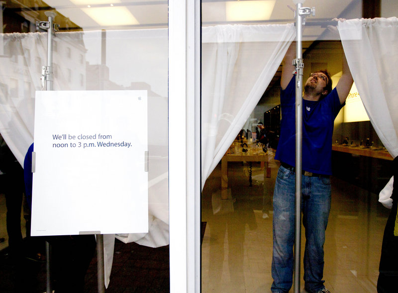 An Apple employee hangs curtains in the front window of a closed store Wednesday in Washington to obstruct the view inside. Apple closed a number of its stores for a memorial service for co-founder and CEO Steve Jobs.