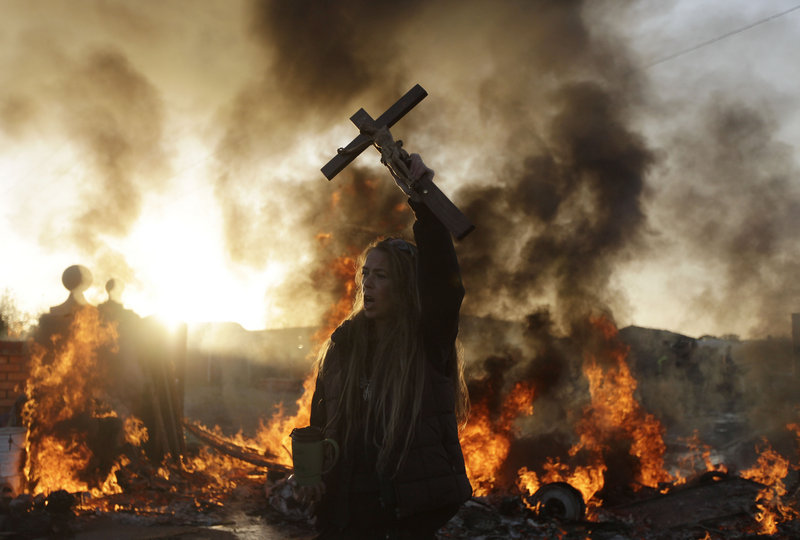 An Irish Traveler holds a cross in front of a burning barricade during Wednesday's evictions.