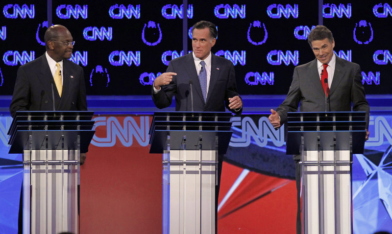 At the presidential candidate debate Tuesday in Las Vegas, Republican Herman Cain, left, watches former Massachusetts Gov. Mitt Romney, center, spar with Texas Gov. Rick Perry.