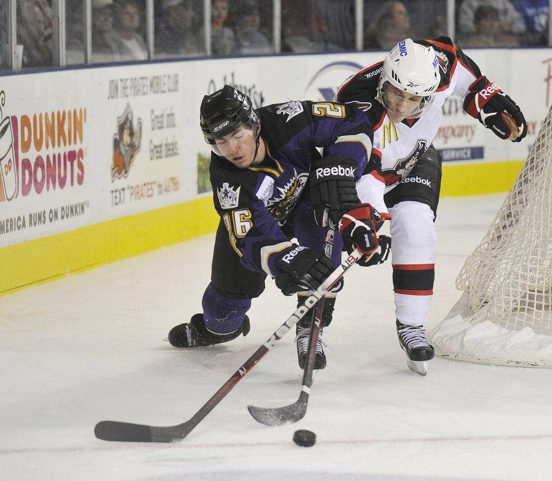 Brandon Kozun of the Manchester Monarchs, left, competes with Andy Miele of the Portland Pirates for the puck Wednesday night during the Pirates 5-3 victory.