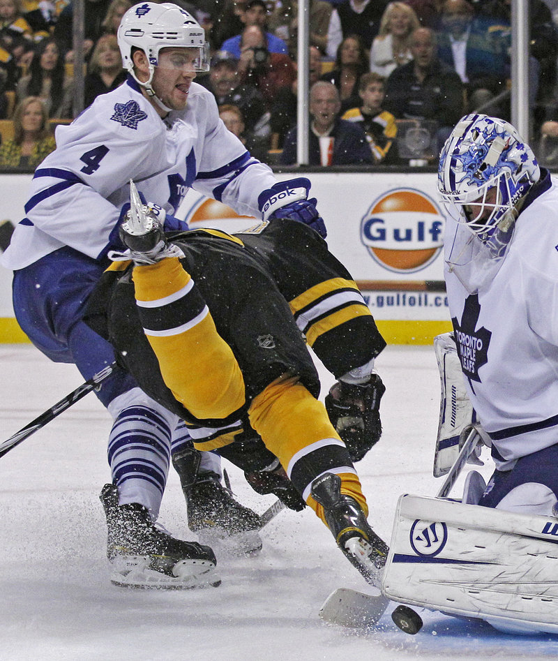 Toronto defenseman Cody Franson, left, knocks down Boston's Brad Marchand after goalie Jonas Gustavsson makes the save.