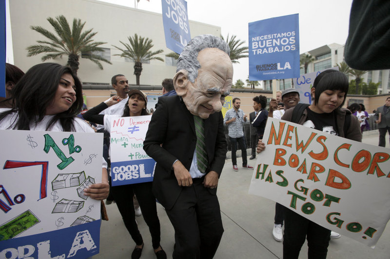 A protester dressed as News Corp. CEO Rupert Murdoch is seen with other demonstrators at Fox Studios in Los Angeles on Friday.
