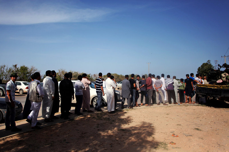 Libyans line up to view Moammar Gadhafi's body in Misrata, Libya, on Friday. Burial has been delayed until circumstances of his death are further examined and a decision is made about where to bury the body.