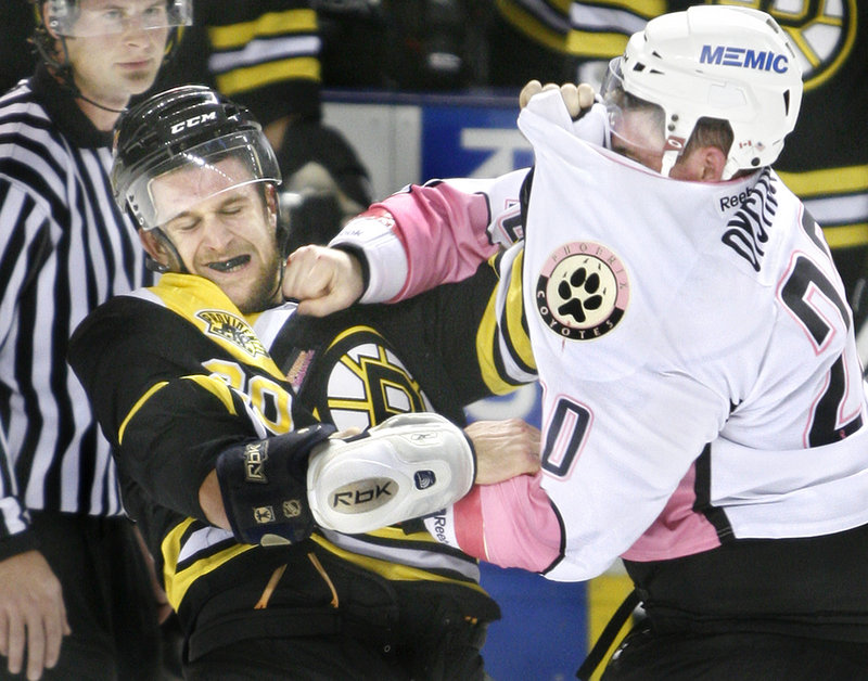 Nathan Oystrick of the Portland Pirates lands a punch on Lane MacDermid of the Providence Bruins despite having his jersey over his eyes. Providence won, 4-3.