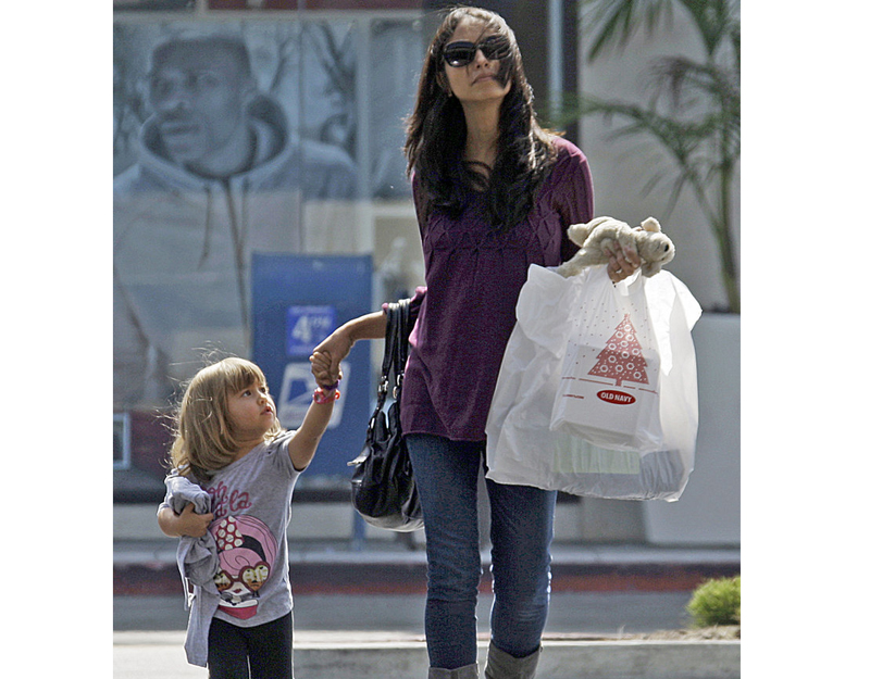 A woman and child leave a mall with purchases recently in Culver City, Calif. Economists say consumer confidence doesn't necessarily track with how they spend their money.