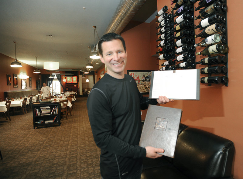 Owner Eric Agren holds a menu and the restaurant's extensive international wine list at Fuel.