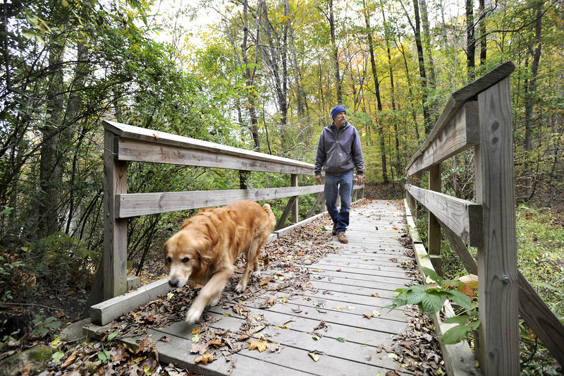 Tim Hopkins of Portland and his dog Minie cross a bridge in a section of the Sebago to the Sea Trail in the Riverton Trolley Park in Portland. A new stretch of the trail, from South Windham to Falmouth, opens today.