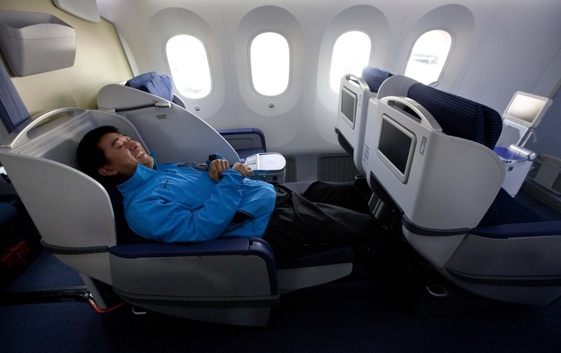 Kang Kang of China Central TV reclines aboard a new Boeing 787.
