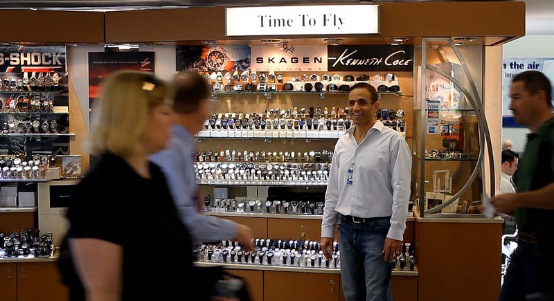"Ben Cohen, owner of ""Time To Fly"" in Philadelphia International Airport's Terminal B, talks with passengers as they walk by his kiosk. For 16 years, Cohen has operated a cart at the airport selling watches priced from $25 to $900."