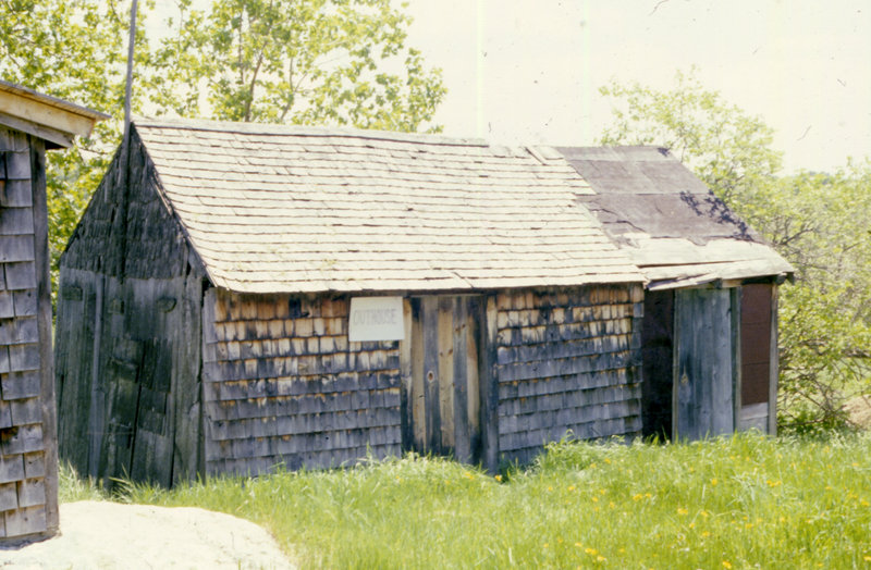 The original privy shed, shown in the early 1980s. The two-seat privy was located along the left side of the shed, which was built in the mid-1800s. Tools and other necessities were stored in the central part of the shed. The door to the right leads to a milk storage area added in the 1930s.