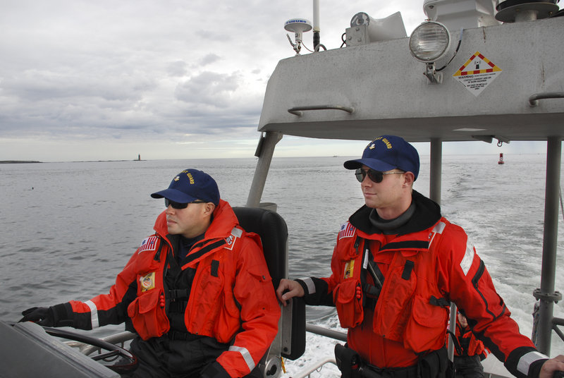 Boatswain's Mates Second Class Ruben A. Colon, left, and Jon Gielarowski patrol Casco Bay on a 47-foot motor lifeboat out of South Portland on Oct. 22.
