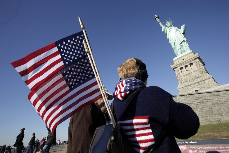 Donna Bodkins of Fisher, W.Va., carries American flags while visiting the Statue of Liberty on the landmark's 125th anniversary Friday in New York. The statue was a gift from France and was dedicated on Oct. 28, 1886.