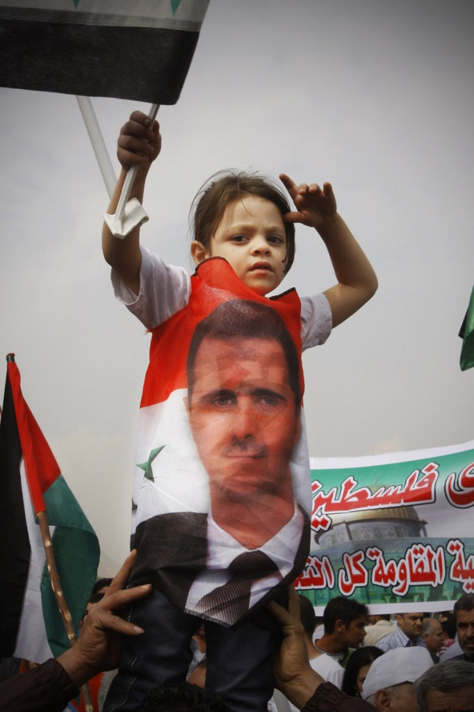 A child looks on during a rally in support of Syrian President Bashar Assad in downtown Damascus on Wednesday. Security forces opened fire on protesters Friday, killing about 30.
