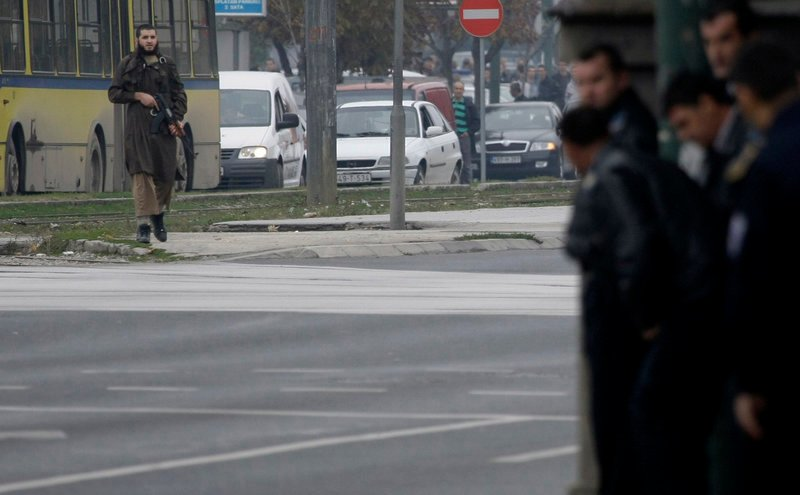 Gunman Mevlid Jasarevic carries an automatic weapon in front of the U.S. Embassy in Sarajevo, Bosnia, on Friday.