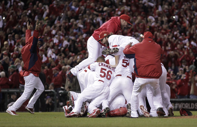 The Associated Press The St. Louis Cardinals pile on each other at Busch Stadium on Friday night after winning the World Series at home.