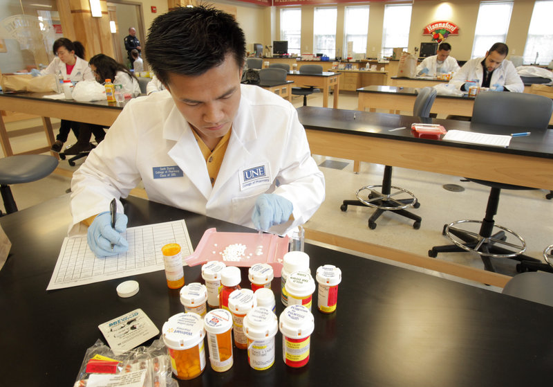 Sanh Duong, a first-year pharmacy student at the University of New England, counts medication that was turned in to the school, which was participating in a national drug take back day on Saturday.