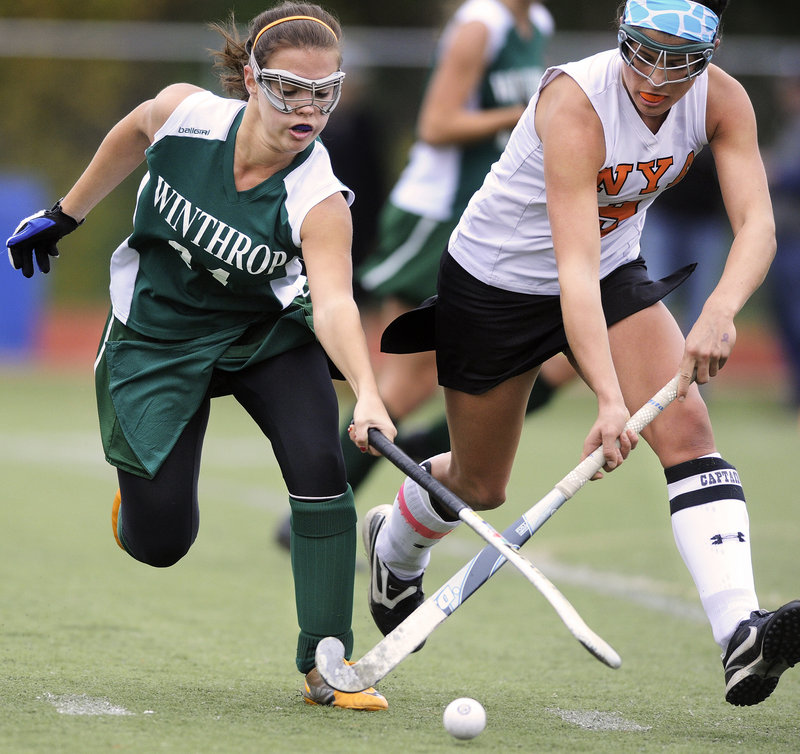 Elizabeth Glover, left, of Winthrop battles with NYA's Katie Millett during the Class C field hockey championship game Saturday at Yarmouth High. NYA won its second straight title, beating the Ramblers in penalty corners.