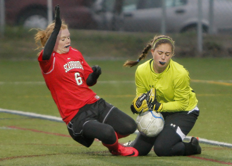Andrea Tolman of Scarborough, left, challenges Cape Elizabeth keeper Ali Johnson on Saturday during their regional semifinal in Cape Elizabeth. Scarborough won, 2-1.
