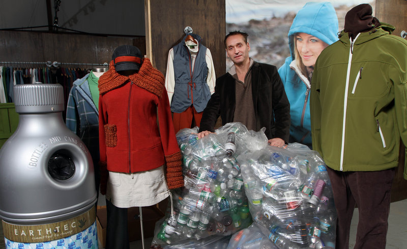 Earthtec founder Dennis Randall stands in his warehouse in Portsmouth, N.H., with bags of recycled bottles and outfits made from recycled bottles. Portland, Ore., is trying to get him to build a manufacturing plant there.