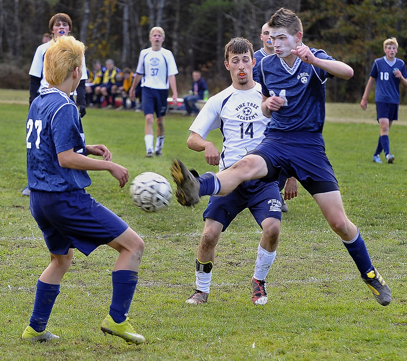 Than Peterson of Greater Portland Christian kicks the ball away from Pine Tree Academy's Joe Reed as Jam Jung, left, looks on during their Western Class D quarterfinal Wednesday in Freeport. Pine Tree won, 5-0.
