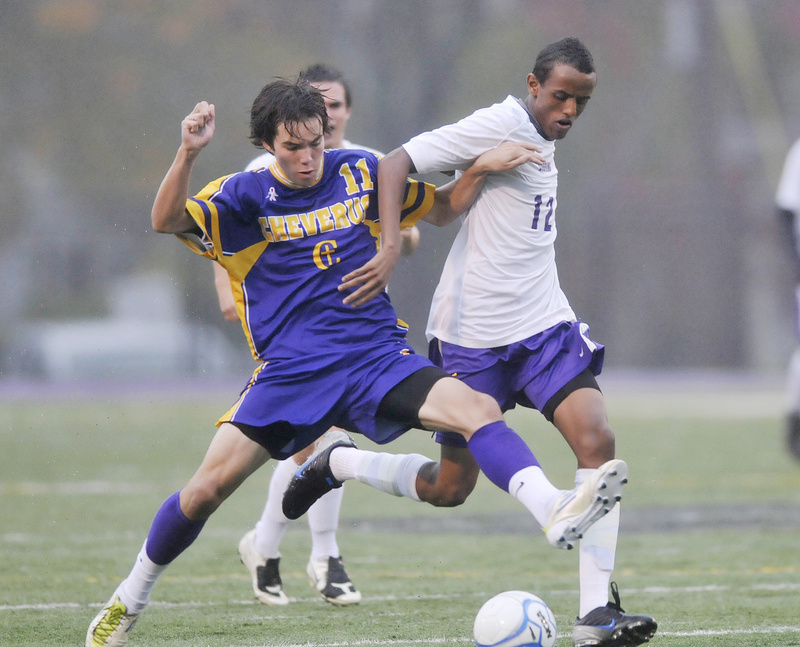 Elliot Maker of Cheverus, left, competes with Abdi Hassan of Deering for the ball Thursday night during their Southern Maine Activities Association schoolboy soccer game. Maker scored twice as the Stags earned a 3-0 victory at Deering High.