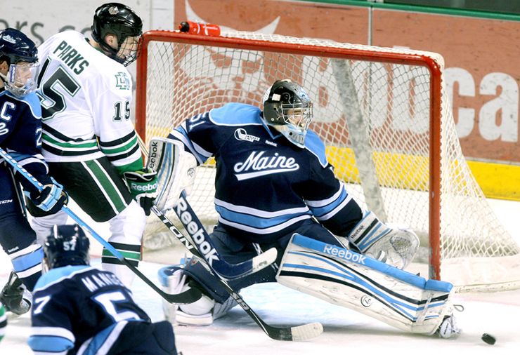 University of Maine goalie Martin Ouellette kicks aside a shot by North Dakota's Michael Parks for one of his 18 saves Friday night in North Dakota's 3-1 victory at Grand Forks, N.D.