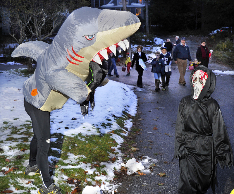 """Dressed as the shark from """"Jaws,"""" John Taxter scares Thomas Pender, 8, who was just as scary in his """"Scream"""" mask."""