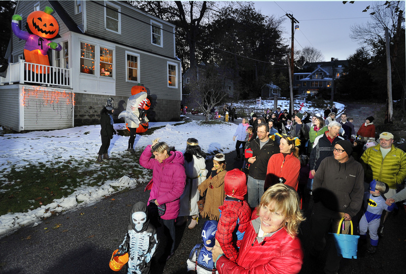 Costumed kids and parents pass the Halloween-themed home of John Taxter during the Falmouth Halloween Parade through the Falmouth Foreside Town Landing neighborhood Monday.