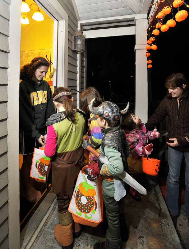 Caitlin Bucksbaum, 16, hands out treats to trick-or-treaters at the family home on Casco Terrace on Monday.