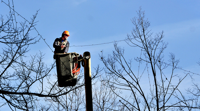 Greg Smith, who works with the forestry division of Portland's Public Services Department, uses a boom truck Monday to put lights for the coming holiday season in the trees around Monument Square. Smith said it takes him and his co-workers, Jay Ash-Cuthbert and Mike Grant, about two weeks to string all of the lights.