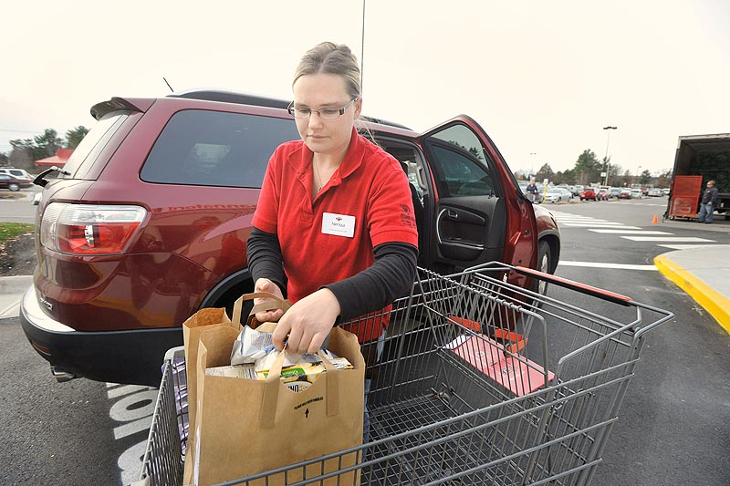 Photo by John Ewing/staff photographer... Tuesday, November 22, 2011. Hannaford's is launching a new service, Hannaford to Go, which allows shoppers to order groceries online and then pick their completed order at the store and into their car. Hannaford associate Nerissa Forbes loads groceries into Hannaford to Go customer Angela Libby's car at the North Windham store.