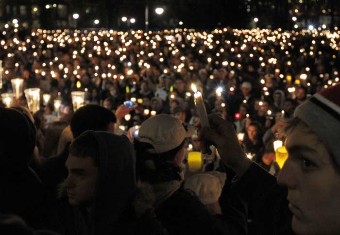 People hold candles during a candlelight vigil in front of the Old Main building on the Penn State Campus Friday, Nov. 11, 2011 in State College, Pa. The vigil is being held in support of the alleged victims of a child sex abuse scandal involving a former assistant coach. (AP Photo/Alex Brandon)