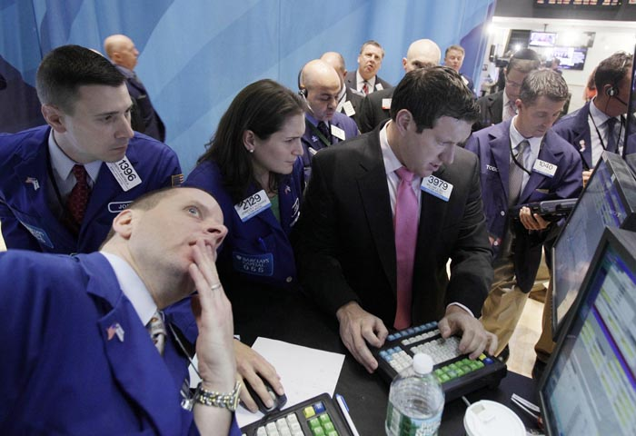 Specialists Jennifer Klesaris, and William Bott, right center, work at a post on the floor of the New York Stock Exchange today.