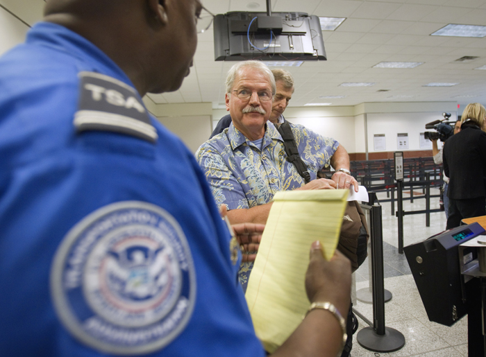 Passenger Don Heim, right, of Alpharetta, Ga., is briefed by Transportation Security Administration trainer Byron Gibson before going through a new expedited security line recently at Hartsfield-Jackson International Airport in Atlanta.