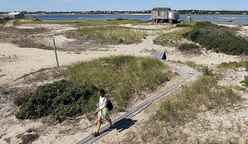 In this Aug. 23, 2011, photo, Susan Carroll, an occupant of one of the 11 cottages on North Beach Island in Chatham, Mass., walks from the beach to her cottage. On Tuesday, the Keeper of the National Register of Historic Places denied protection for five of the cottages slated to be torn down, saying they aren't rare or historically important enough to qualify for the list. The decision means their owner, the federal Cape Cod National Seashore, can proceed with demolition.