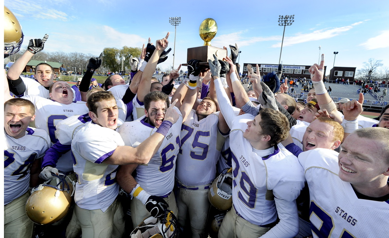 Cheverus players hoist the Gold Ball for the second year in a row after beating Lawrence 49-7 to win the Class A football state championship.
