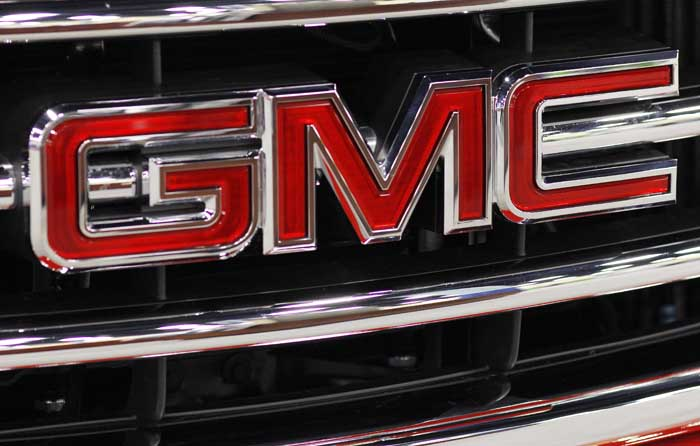 This Oct. 28, 2011 photo, shows the GMC nameplate on the grille of a 2012 GMC Sierra at the 41st annual South Florida International Auto Show, in Miami Beach, Fla. General Motors said Wednesday, Nov. 9, 2011, it earned $1.7 billion in the third quarter, down 15 percent from a year earlier. (AP Photo/Lynne Sladky)