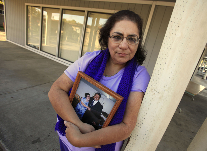 Karen Carrisosa holds a photo of her and her husband Larry, at the site where he was killed in Sacramento, Calif. Carrisosa became concerned when officials found a Facebook posting from Corcoran State Prison inmate Fredrick Garner who is serving a 22-year, involuntary manslaughter sentence for killing Larry 11 years ago.