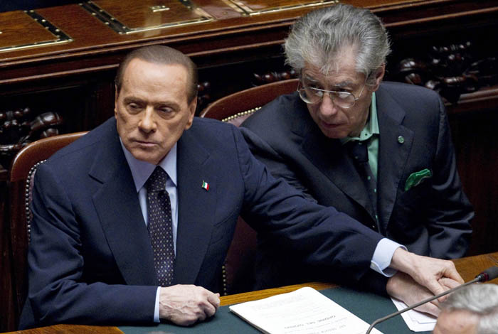 Italian Premier Silvio Berlusconi, left, holds the hand of Reforms Minister Umberto Bossi during a voting session at the Lower Chamber, in Rome, today. Berlusconi won a much-watched vote, but the result laid bare his lack of support in Parliament as financial pressure from the eurozone debt crisis pummeled Italy.