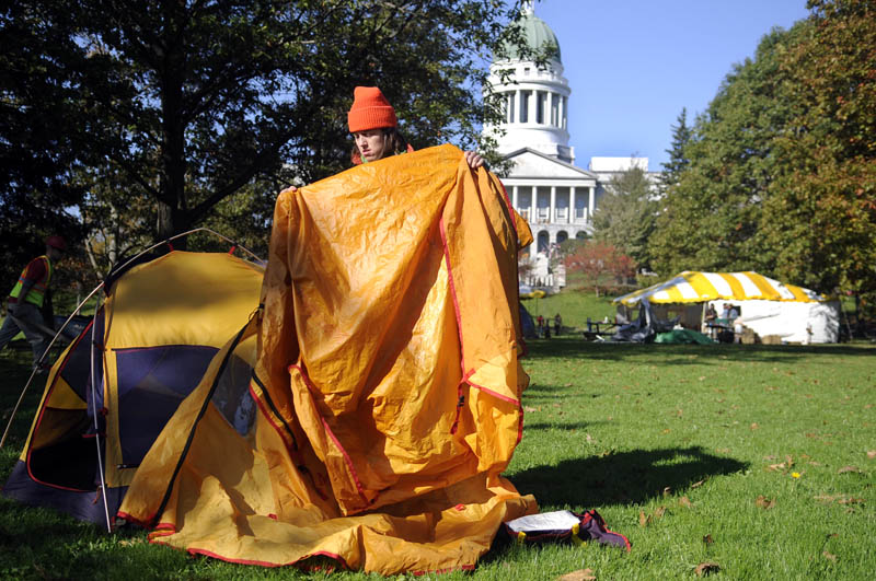 Daphne Loring shakes dew off a tarp Monday morning while breaking down her tent in Capitol Park. The Greene farmer spent two nights in the park as part of the Occupy Augusta protest. Loring said she needed to tend to the hogs she is raising but plans to return to the camp out.