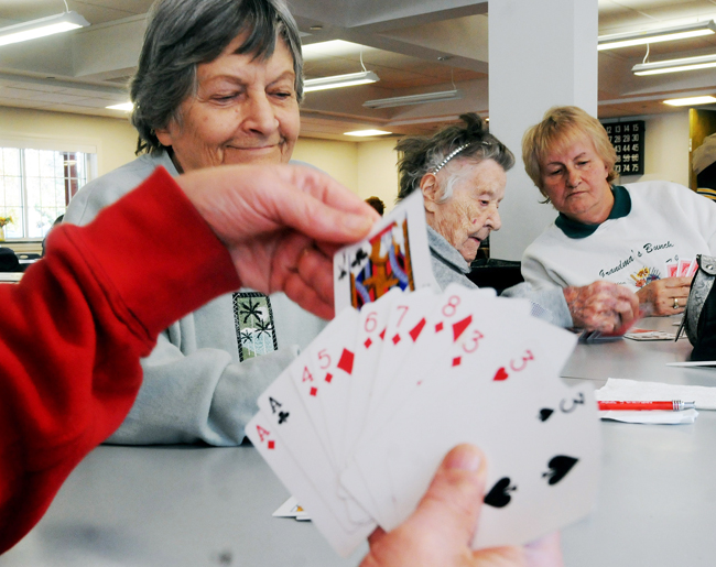 Seniors citizens pass the time playing cards on Tuesday at a shelter in Windsor Conn. Connecticut Gov. Dannel P. Malloy toured telling the 300 people using the center everything possible is being done to restore power.
