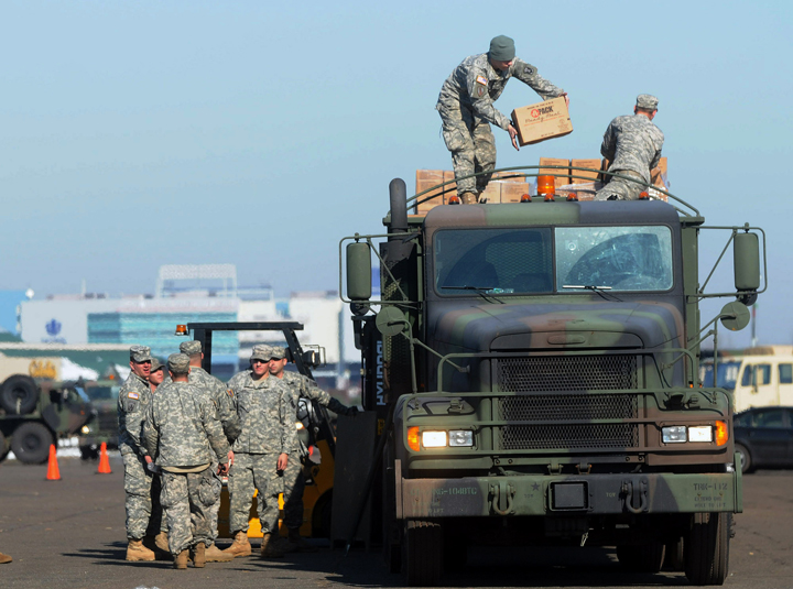 Members of the Connecticut National Guard Air Force and Army on Wednesday load pallets of MRE's (Made Ready to Eat) and bottled water onto a military truck to be shipped out to towns and communities affected by power outages.
