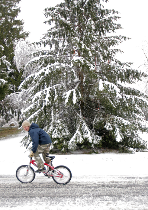 Emil Harmon rides his bicycle along snow-covered Route 117 in Hollis today.