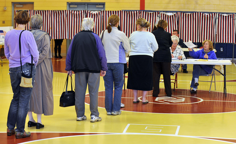 Hana Strnad, right, election clerk at the Boys and Girls Club voting place in South Portland, hands a ballot to a voter while fellow election clerk Linden Thigpen, to Strnad's left, verifies the each voter's eligibility.